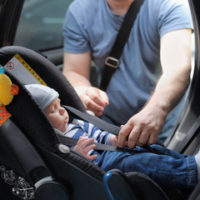 father putting kid in car seat