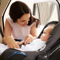 Mother Putting Baby Son in rear-facing car seat
